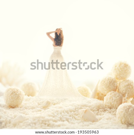Woman in white dress in a fairy world of big candies. Unusual modern art - stock photo