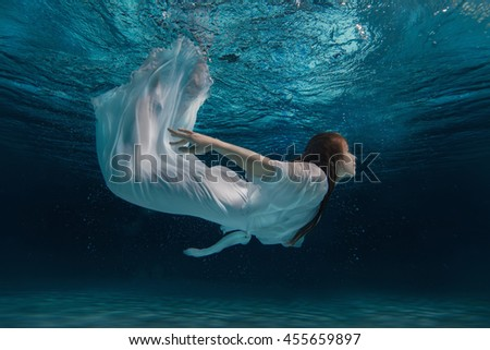 Woman in white dress swimming under water like a mermaid amid bursts. - stock photo