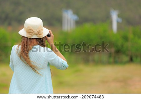 Woman in white dress taking photo of wind turbines - stock photo