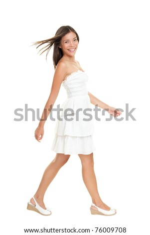 Woman in white dress walking isolated on white in full length.  Beautiful fresh smiling young mixed race Asian Caucasian female model in cute summer dress. - stock photo