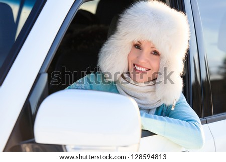 woman in white fur hat in a car smiling to you. - stock photo