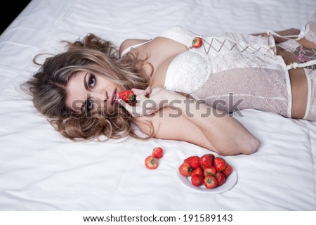 woman in white lingerie eating strawberry in her bedroom - stock photo