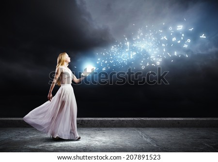Woman in white long dress with book in hands - stock photo