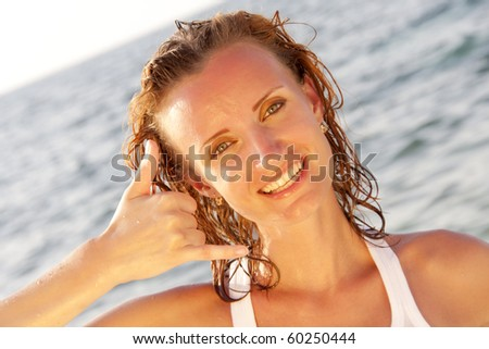 """Woman in white on the beach shows """"Call me"""" sign - stock photo"""