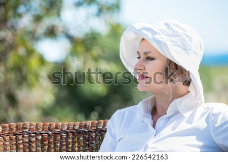 Woman in white sitting on a wicker bench and looking away  - stock photo