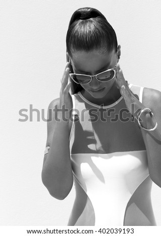 Woman in white swimsuit and golden sunglasses with hair up poses on isolated background - stock photo