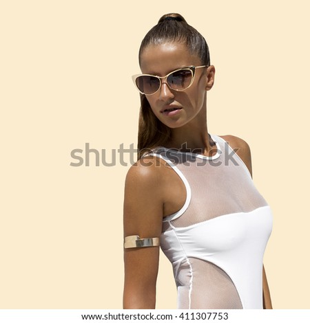 Woman in white swimsuit and golden sunglasses with hair up poses on isolated background. High fashion shot.  - stock photo