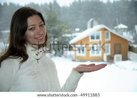 Woman in winter clothes showing new house - stock photo