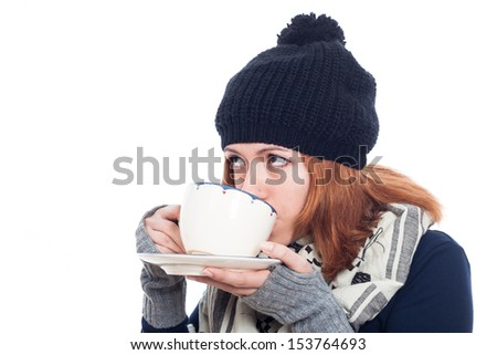 Woman in winter hat drinking hot tea or coffee, isolated on white background. - stock photo