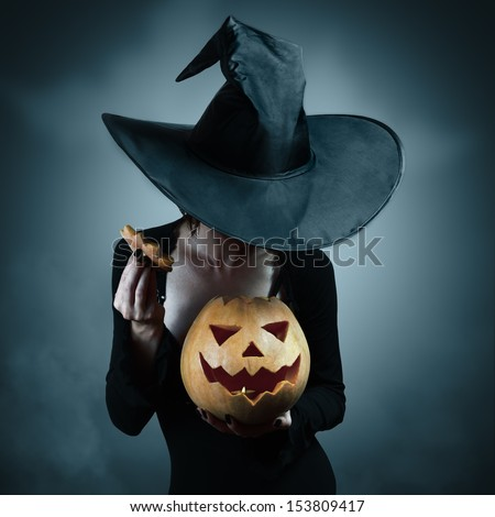 Woman in witch costume opens carved Halloween pumpkin - stock photo