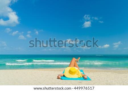 Woman in yellow bikini lying on tropical beach at Seychelles - stock photo