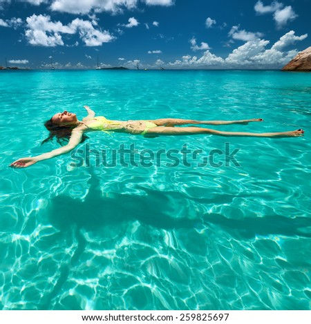 Woman in yellow bikini lying on water at tropical beach - stock photo