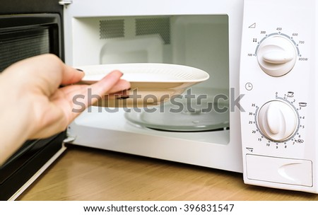 woman includes microwave oven, power and time of microwave ovens, warming food in a dish - stock photo