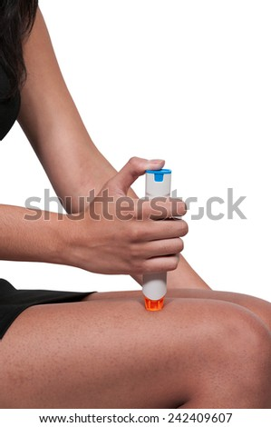 Woman injecting emergency medicine into her leg - stock photo