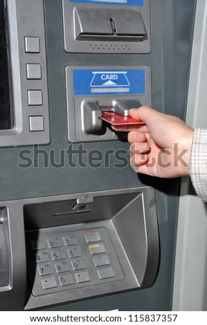 Woman insert card to withdraw money - stock photo