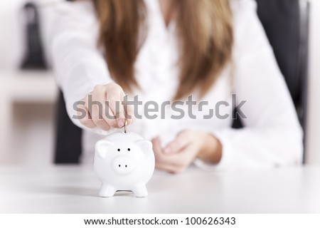 Woman inserting coins in the piggy bank at her office (selective focus on the coin) - stock photo