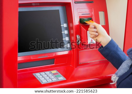 Woman inserting credit card into ATM to withdraw money - stock photo