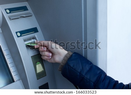 Woman inserting her bank card at the ATM outside a bank so that she can withdraw cash by entering her pin code - stock photo