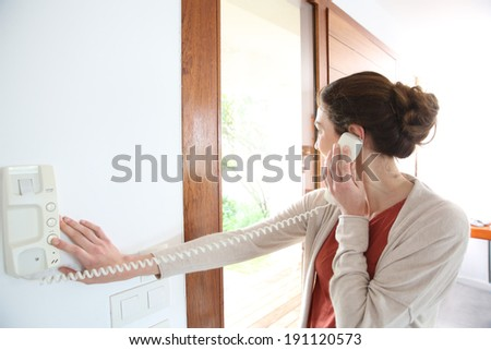 Woman inside home answering security phone - stock photo