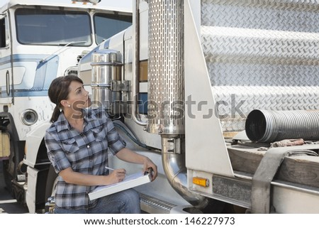 Woman inspecting flatbed truck - stock photo