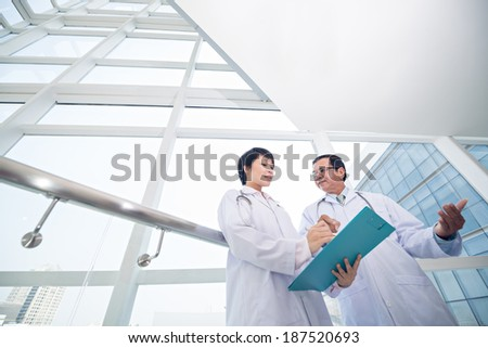Woman intern and middle-aged doctor discussing diagnosis - stock photo