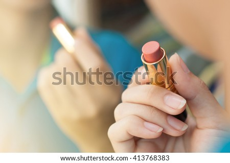 Woman is applying makeup and looking in the mirror. Closeup of red lipstick. Hand of woman is holding lipstick. - stock photo