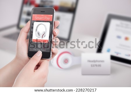 Woman is buying headphones by black mobile smart phone with nfc smart pay application on the screen. Purchase of headphones by fingerprint scanning in smart pay application. - stock photo
