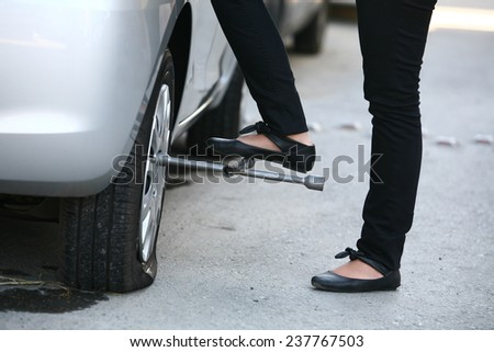 Woman is changing tire of her car with wheel wrench.  - stock photo