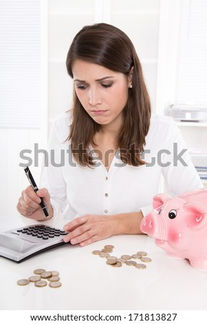Woman is counting her money - sitting sad at desk and has lost her dreams - stock photo