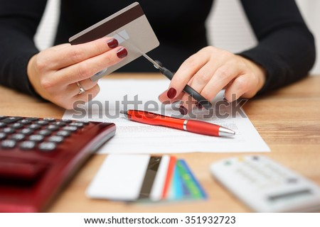 woman is cutting credit card or bank card with scissors over contract and other credit cards - stock photo