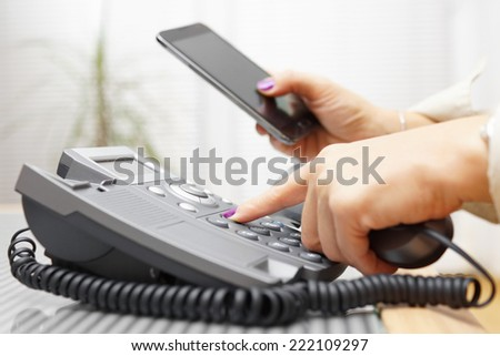 Woman is dialing on land line phone and looking on mobile phone - stock photo