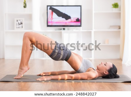 Woman is doing fitness at home on her living room floor while watching and participating in a class. - stock photo