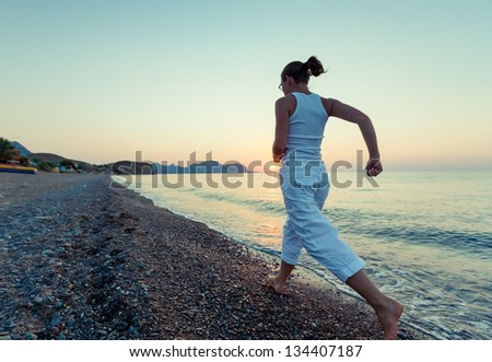 Woman is doing morning excercises at the sea during sunrise - stock photo