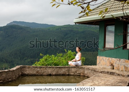 Woman is doing yoga exercises in mountains - stock photo