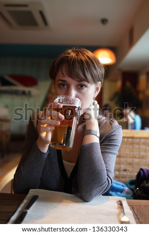 Woman is drinking beer in a pub - stock photo