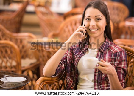 Woman is drinking coffee in the cafe and talking to mobile phone. - stock photo