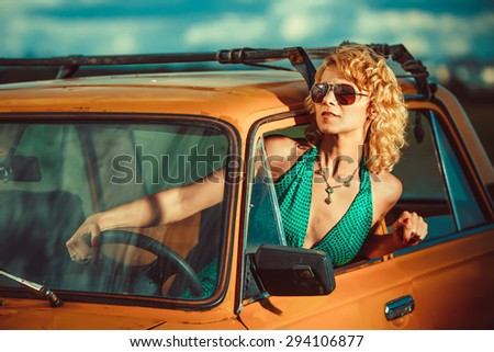 Woman is driving an old yellow car. Rural background. - stock photo