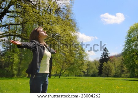 Woman is  enjoying her life  among trees on spring sun outdoors in park - stock photo