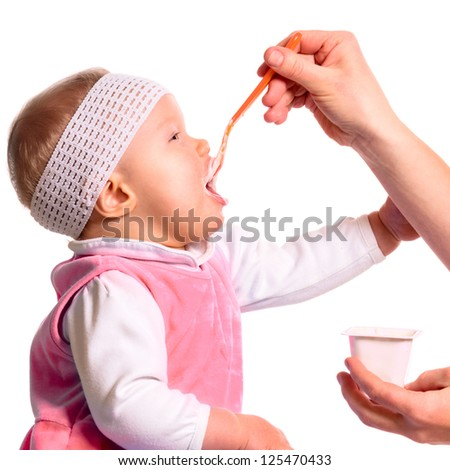 woman is feeding her baby with a spoon - stock photo