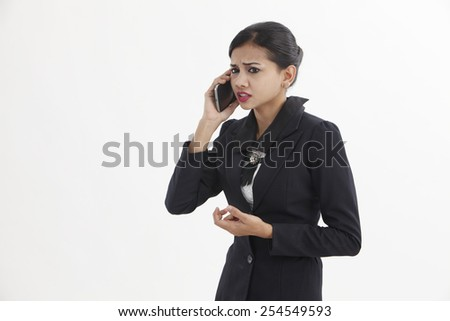 woman is feeling sad as she is talking on here mobile cell phone. A young woman being sad. - stock photo