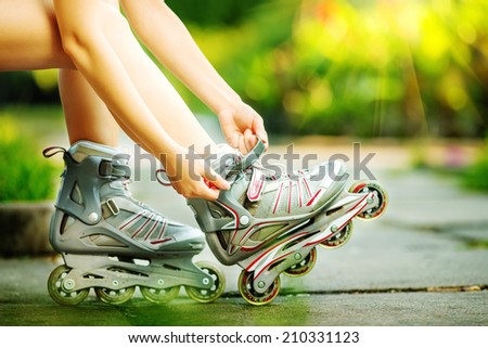Woman is going rollerblading. Sitting on a bench in a park and putting on inline skates. Close up. Sport lifestyle. - stock photo