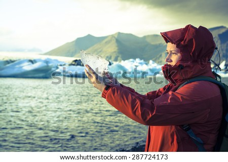 Woman is holding a piece of ice from the glacier at Jokulsarlon Lagoon in Iceland. Cross-processed treatment - stock photo