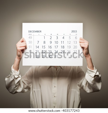 Woman is holding December calendar of the year two thousand fifteen - stock photo