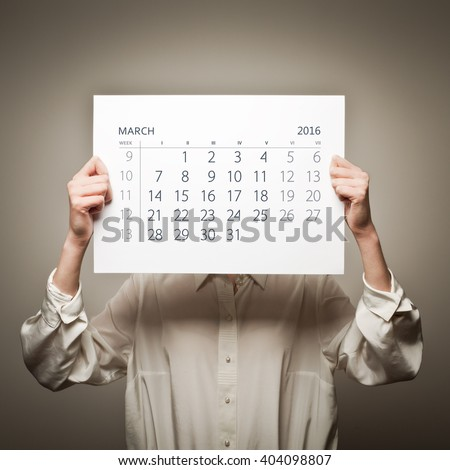 Woman is holding March calendar of the year two thousand sixteen. - stock photo