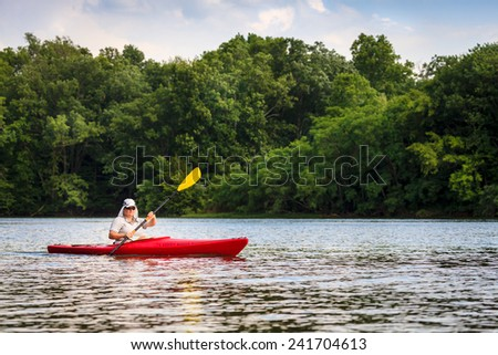 Woman is kayaking on a small lake in Central Kentucky - stock photo