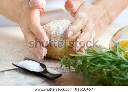 Woman is kneading fresh dough balls in the bakery. Ingredients for dough: salt, olive oil and fresh herbs - stock photo