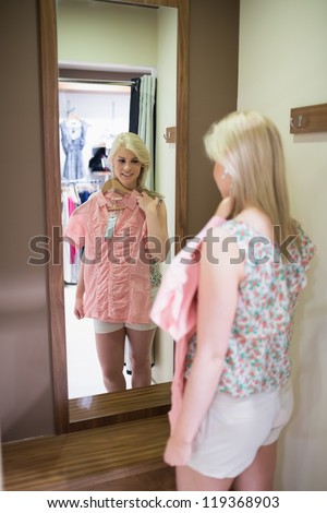 Woman is looking in mirror holding up shirt - stock photo