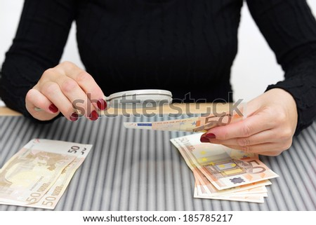 woman is looking through a magnifying glass for counterfeit money - stock photo