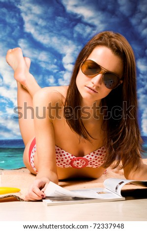 woman is lying at beach, dramatic skies - stock photo