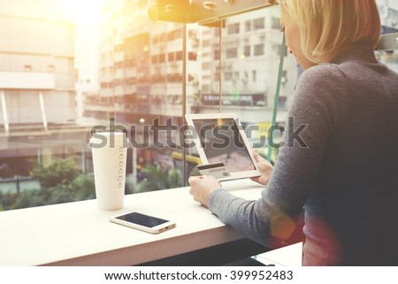 Woman is making an on-line purchase via touch pad, while is sitting in cafe with Overlooking the main street of New York. Female is using credit card for shopping in internet store via digital tablet - stock photo